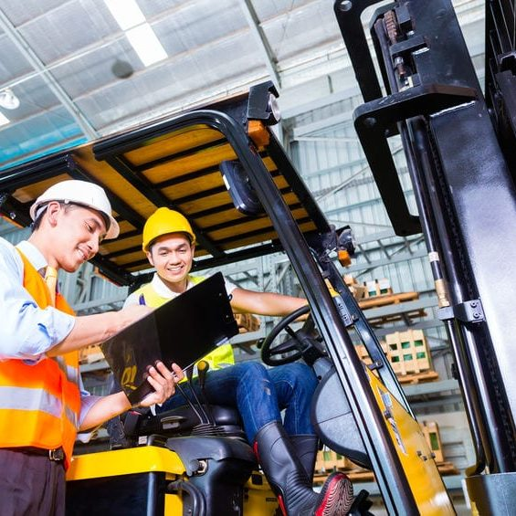 fork lift truck driver discussing checklist with foreman in warehouse